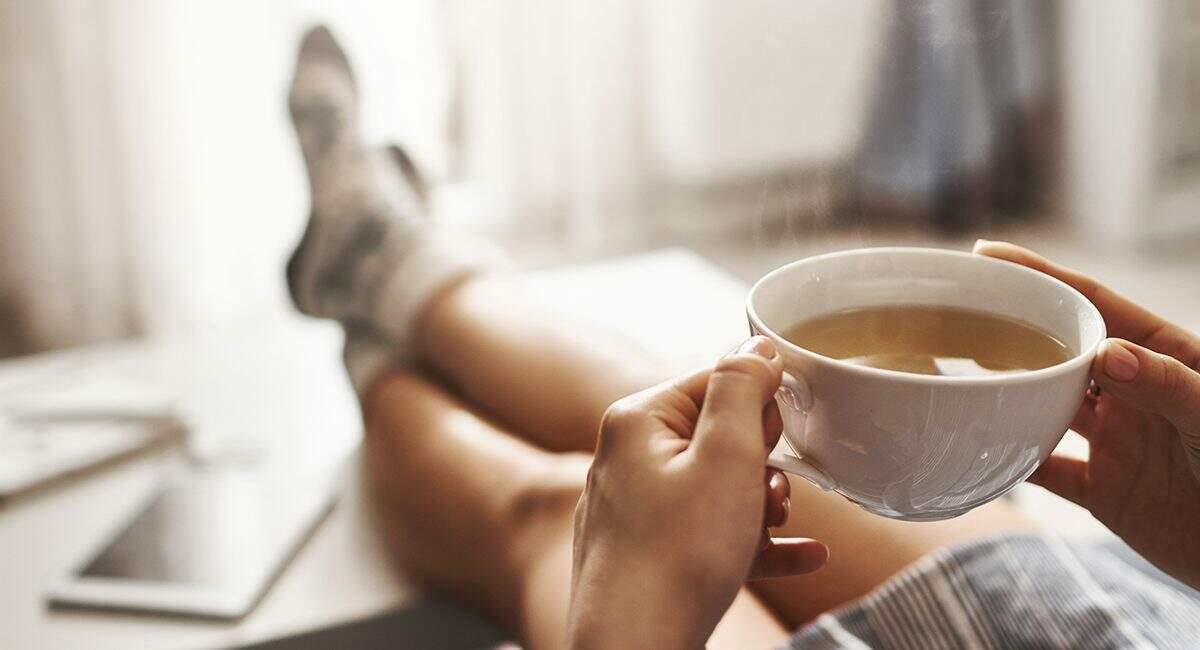Cup of tea and chill. Woman lying on couch, holding legs on coffee table, drinking hot coffee and enjoying morning, being in dreamy and relaxed mood. Girl in oversized shirt takes break at home.